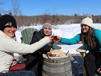 Friends drinking wine outside in Winter at Muskoka Lakes Winery